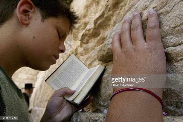 Jewish youth Yehuda Holzer from Long Island New York wears his Kabbalah Red String Bracelet while praying at the Western Wall Judaism's holiest site...
