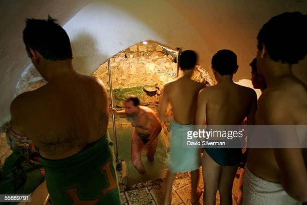 Jewish youths wait their turn to immerse themselves as a religious Jewish man leaves the icy waters of a ritual bath attributed to Rabbi Yitzhak...