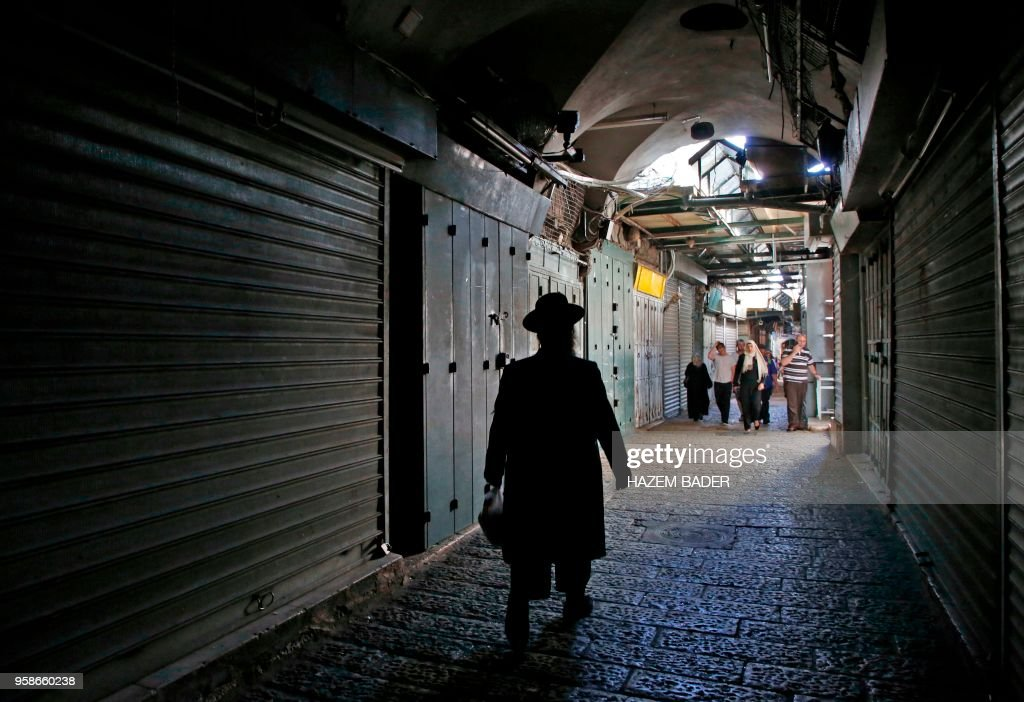 TOPSHOT - Jews and Muslims walk past closed shops in the Old City of Jerusalem on May 15, 2018, during a general strike in solidarity with those killed in Gaza during protests against the US embassy's move to Jerusalem.