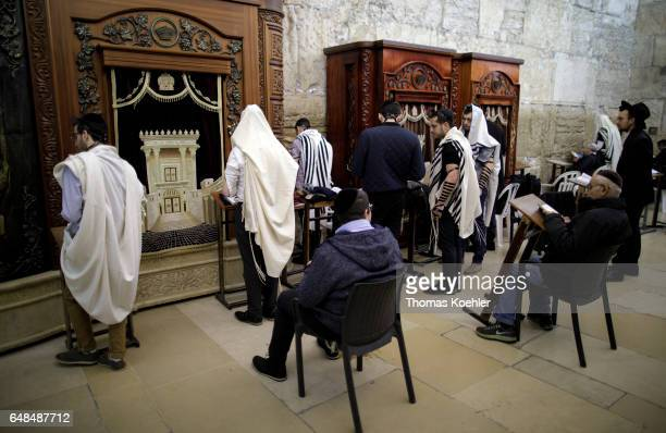 Jews are praying in a hallway next to the Wailing Wall in the historic city center of Jerusalem The wooden shrines serve to store the Holy Scripture...