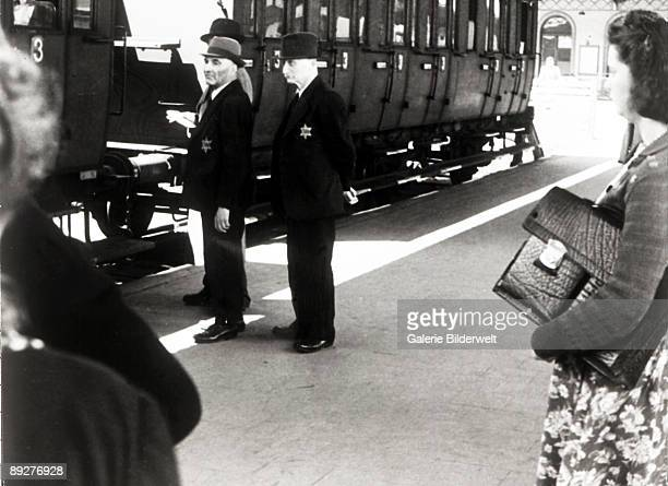 Jews waiting for the train whilst being deported from Hanau Germany 30th May 1942 They are wearing the star emblem which identifies them as Jewish