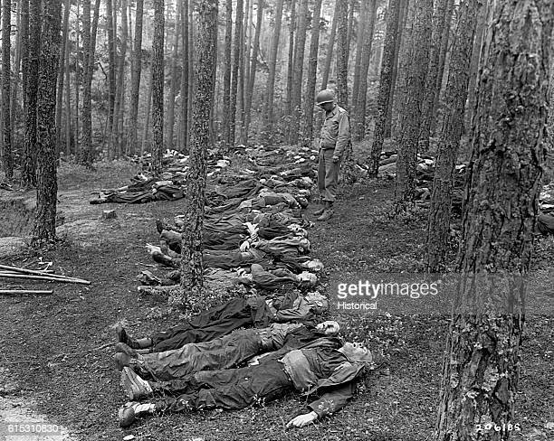 Jews who had been used for slave labor in Neunburg, now lying dead on the forest floor with a soldier standing over them. | Location: forest,...