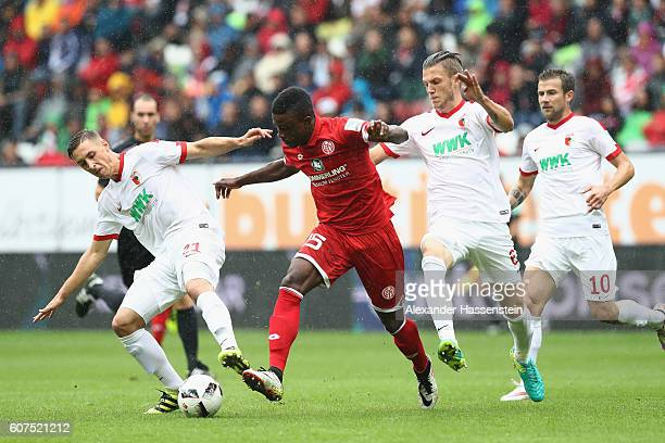 Jhon Andrés Córdoba Copete of Mainz battles for the ball with Dominik Kohr of Augsburg and his team mate Jeffrey Gouweleeuw during the Bundesliga...