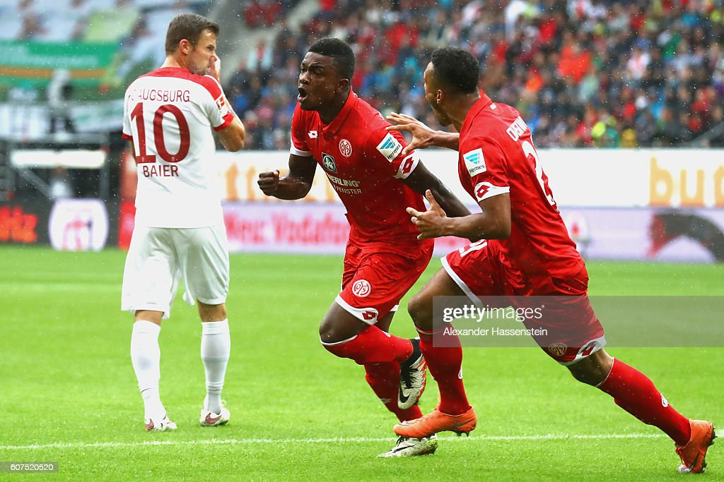 Jhon Andrés Córdoba Copete (C) of Mainz celebrates scoring the opening goal with his team mate Karim Onisiwo whilst Daniel Baier (L) of Ausgburg looks on during the Bundesliga match between FC Augsburg and 1. FSV Mainz 05 at WWK Arena on September 18, 2016 in Augsburg, Germany.