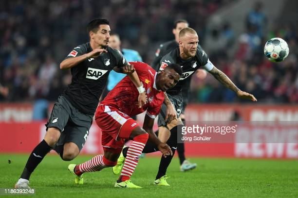 Jhon Cordoba of 1. FC Koeln is challenged by Benjamin Hubner and Kevi Vogt of TSG 1899 Hoffenheim during the Bundesliga match between 1. FC Koeln and...