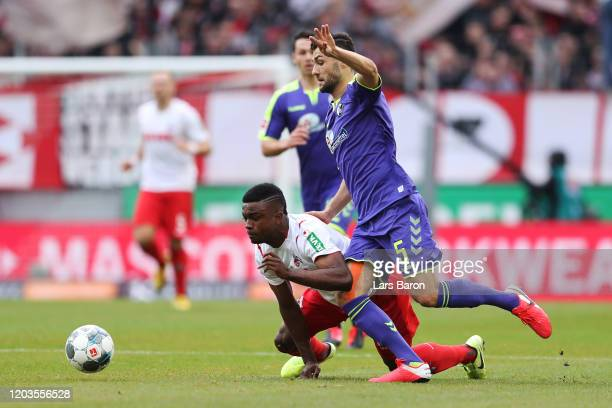Jhon Cordoba of FC Koln is tackled by Manuel Gulde of SC Freiburg during the Bundesliga match between 1 FC Koeln and SportClub Freiburg at...