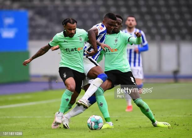 Jhon Cordoba of Hertha Berlin battles for possession with Valentino Lazaro of Borussia Moenchengladbach and Denis Zakaria of Borussia...