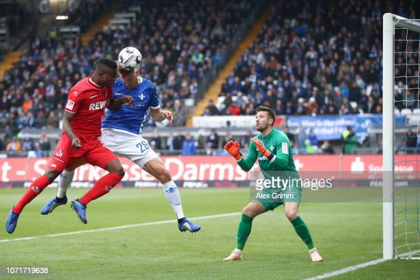 Jhon Cordoba of Koeln attempts to score with a header against Marcel Franke and goalkeeper Daniel Heuer Fernandes of Darmstadt during the Second...