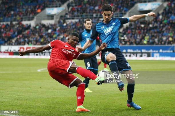 Jhon Cordoba of Mainz is challenged by Benjamin Huebner of Hoffenheim during the Bundesliga match between TSG 1899 Hoffenheim and 1 FSV Mainz 05 at...