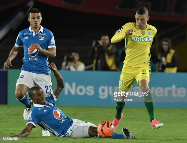 Jhon Duque Arias and Jair Palacios of Millonarios fight for the ball with Mateus Andres Uribe of Atletico Nacional during the Semi Finals first leg...