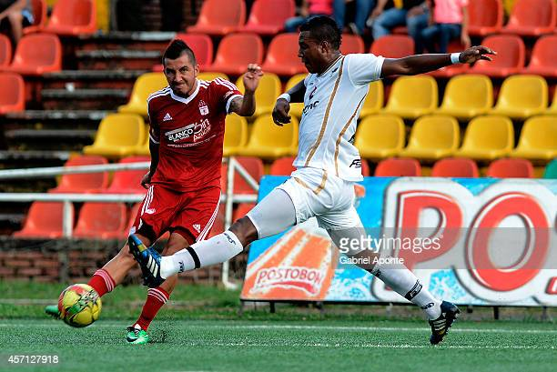 Jhon Fredy Perez of America struggles for the ball with Kevin Riascos of Llaneros FC during a match between America de Cali and Llaneros FC as part...
