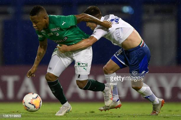 Jhon Vásquez of Deportivo Cali competes for the ball with Tomás Guidara of Velez during a round of sixteen first leg match between Velez and...