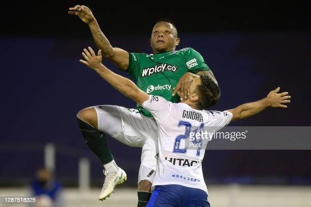 Jhon Vásquez of Deportivo Cali jumps for a header with Tomás Guidara of Velez during a round of sixteen first leg match between Velez and Deportivo...