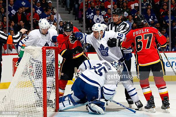 Jhonas Enroth covers the puck as Roman Polak of the Toronto Maple Leafs shoves Matthew Tkachuk of the Calgary Flames during an NHL game on November...