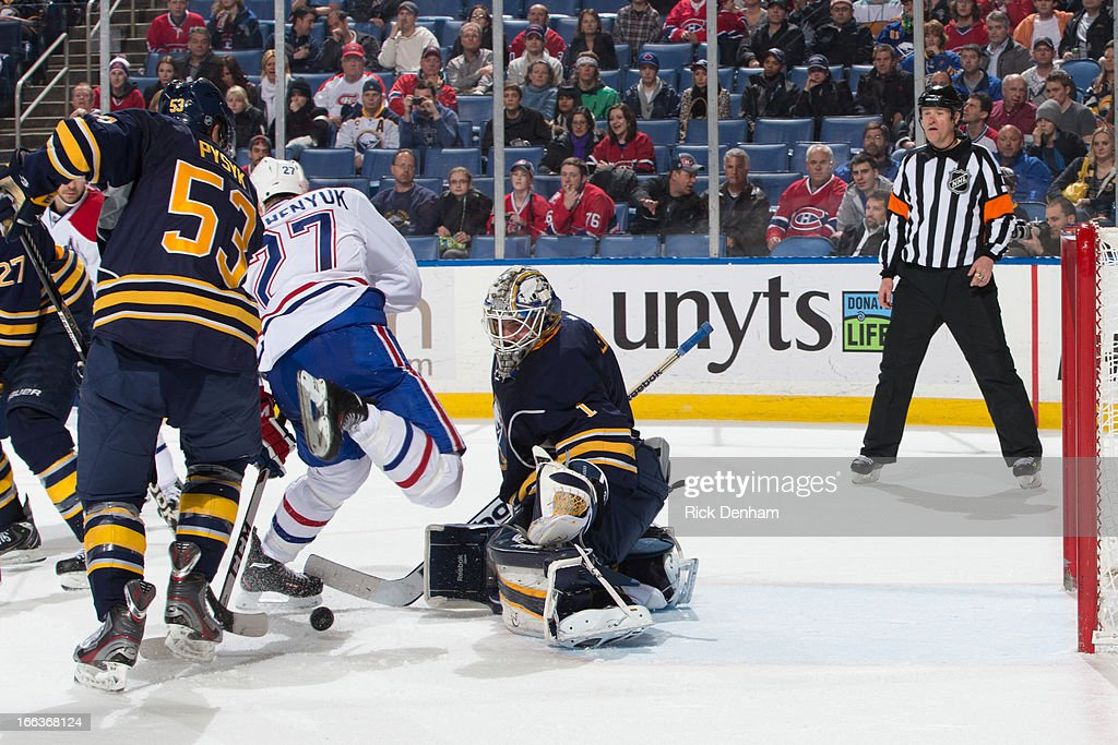 Jhonas Enroth #1 of the Buffalo Sabres looks for a loose puck in front of the net while Alex Galchenyuk of the Montreal Canadiens and Alexander Sulzer #52 of the Buffalo Sabres battle for position during the NHL game at First Niagara Center on April 11, 2013 in Buffalo, New York.