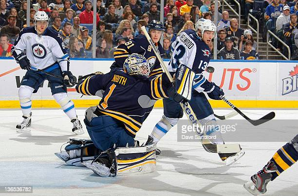 Jhonas Enroth of the Buffalo Sabres makes a blocker save as Kyle Wellwood and Nik Antropov both of the Winnipeg Jets look on as well as Brayden...