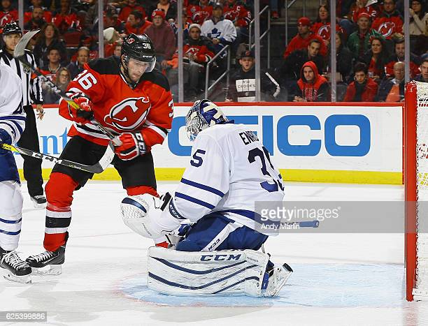 Jhonas Enroth of the Toronto Maple Leafs cannot stop a shot for a goal by Yohann Auvitu of the New Jersey Devils as Nick Lappin looks on during the...