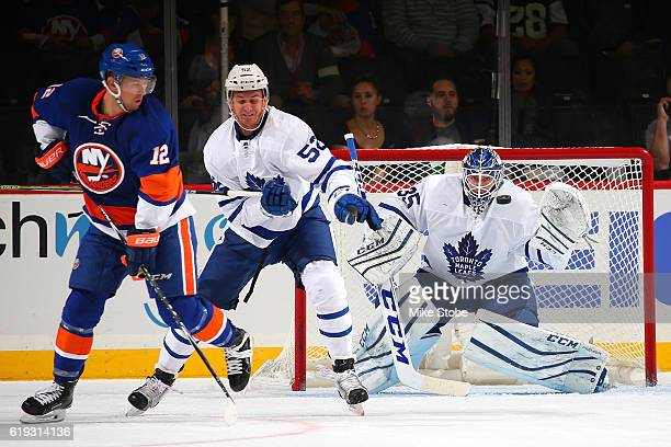 Jhonas Enroth of the Toronto Maple Leafs keeps his eyes on the puck as teammate Martin Marincin and Josh Bailey of the New York Islanders look for...