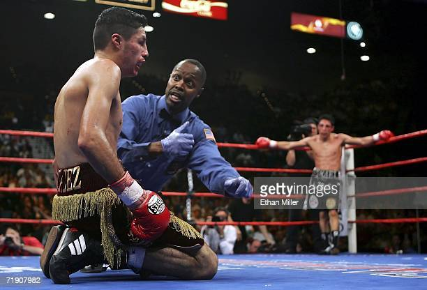 Jhonny Gonzalez of Mexico sits on the mat as referee Kenny Bayless counts as Israel Vazquez waits in the corner in the 10th round during their WBC...