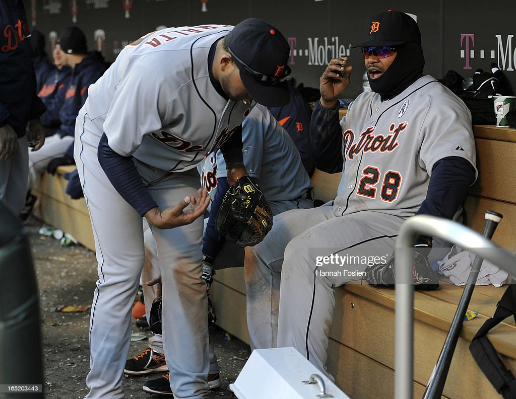Jhonny Peralta #27 and Prince Fielder #28 of the Detroit Tigers warm themselves by a heater in the dugout during a pitching change in the ninth inning of the Opening Day game against the Minnesota Twins on April 1, 2013 at Target Field in Minneapolis, Minnesota. The Tigers defeated the Twins 4-2.