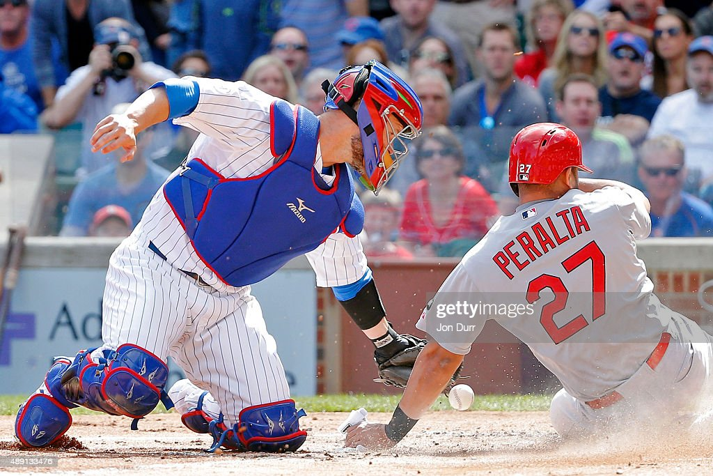 Jhonny Peralta #27 of the St. Louis Cardinals slides safely into home plate as David Ross #3 of the Chicago Cubs is unable to keep control of the ball during the second inning at Wrigley Field on September 19, 2015 in Chicago, Illinois.