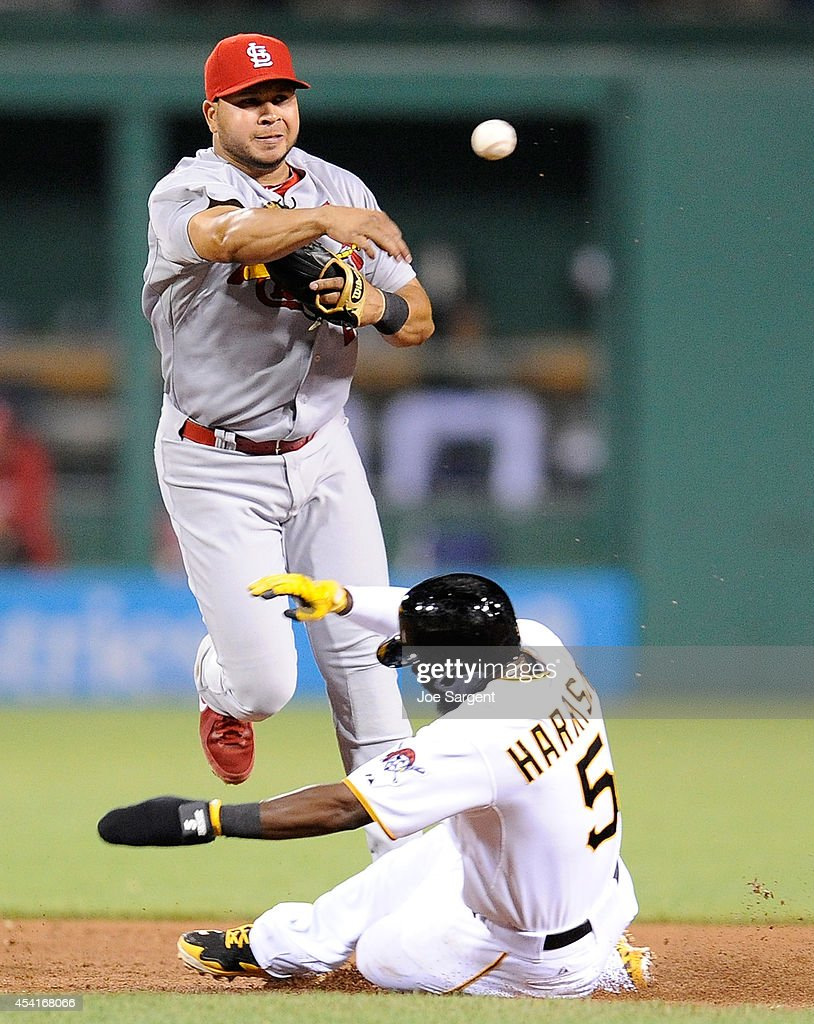 Jhonny Peralta #27 of the St. Louis Cardinals turns a double play in front of Josh Harrison #5 of the Pittsburgh Pirates during the eighth inning on August 25, 2014 at PNC Park in Pittsburgh, Pennsylvania.