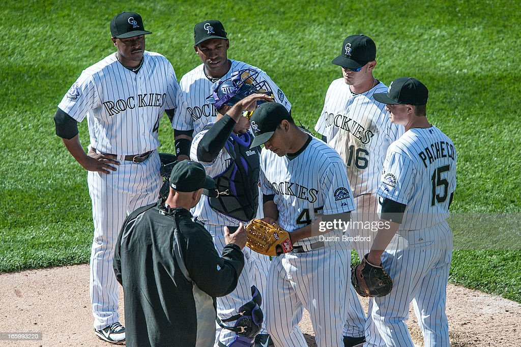 Jhoulys Chacin #45 of the Colorado Rockies is congratulated by teammates (from left, Chris Nelson #4, Jonathan Herrera #18;Reid Brignac #16, Jordan Pacheco #15, and Wilin Rosario #20) as he is relieved by manager Walt Weiss #22 in the seventh inning against the San Diego Padres at Coors Field on April 7, 2013 in Denver, Colorado. The Rockies beat the Padres 9-1.