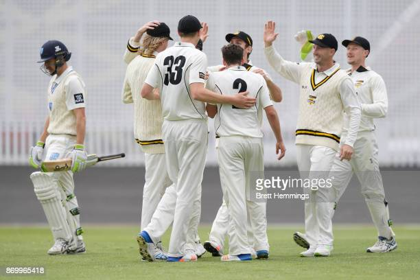Jhye Richardson of WA celebrates with team mates after taking the wicket of Daniel Hughes of NSW during day one of the Sheffield Shield match between...