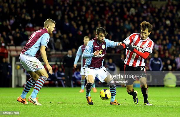 Ji Dong Won of Sunderland tries to tackle Antonio Luna of Aston Villa with Nathan Baker watching during the Barclays Premier League match between...