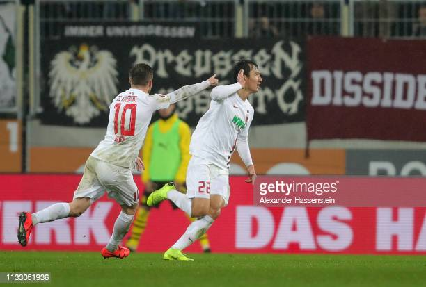 Ji DongWon of Augsburg celebrates scoring his teams second goal during the Bundesliga match between FC Augsburg and Borussia Dortmund at WWKArena on...