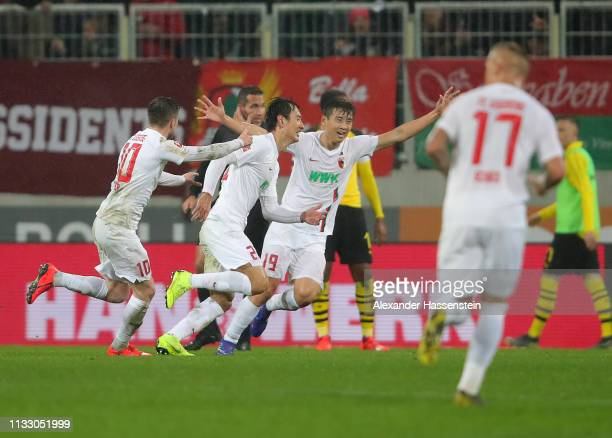 Ji DongWon of Augsburg celebrates scoring his teams second goal with teamates during the Bundesliga match between FC Augsburg and Borussia Dortmund...