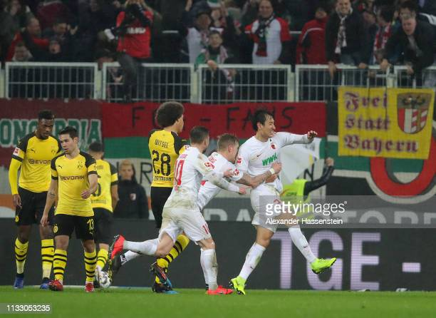 Ji DongWon of Augsburg celebrates scoring his teams second goal with teamates as players of Dortmund look dejected during the Bundesliga match...