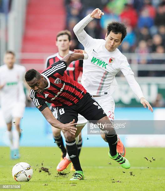 Ji DongWon of Augsburg challenges Roger of Ingolstadt 04 during the Bundesliga match between FC Ingolstadt and FC Augsburg at Audi Sportpark on...
