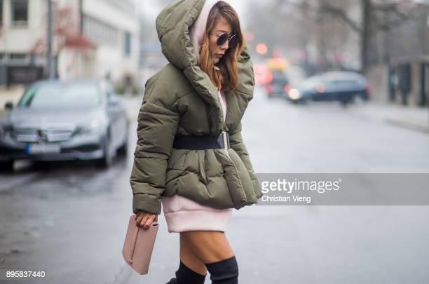 Ji Kim wearing olive belted puffer jacket HM hoodie Nicki Minaj for HM black sock boots Zara Blumbag clutch sunglasses on December 19 2017 in Berlin...