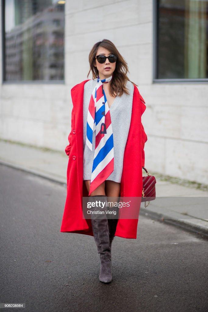Ji Kim wearing red H&M coat, silk scarf Balenciaga, Zara jumper, overknee boots YSL, Saint Laurent bag, Gucci sunglasses is seen during the Berlin Fashion Week January 2018 on January 17, 2018 in Berlin, Germany.