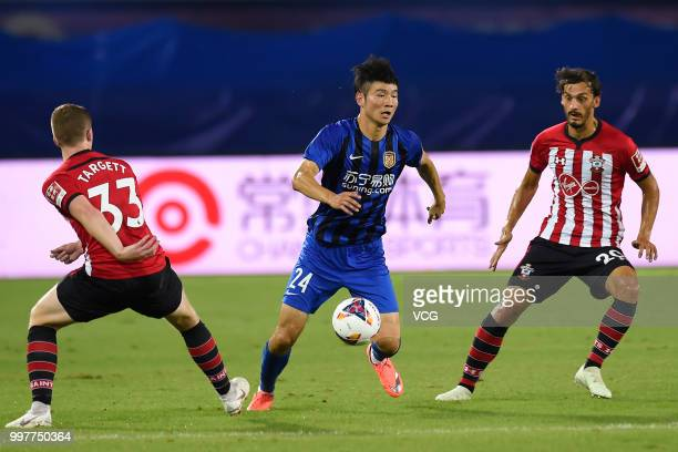 Ji Xiang of Jiangsu Suning and Manolo Gabbiadini of Southampton compete for the ball during the 2018 Clubs Super Cup match between Southampton FC and...