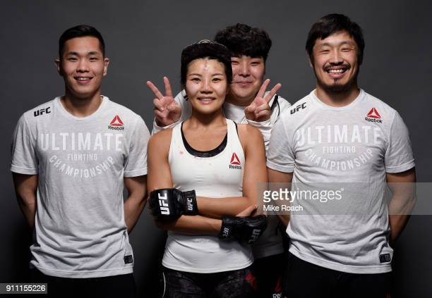 Ji Yeon Kim of South Korea poses for a post fight portraits with her team backstage during a UFC Fight Night event at Spectrum Center on January 27...