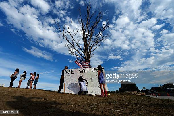 Jia Cummings and Lucy Cummings sign a message board at the makeshift memorial for the 12 movie theater shooting victims built across the street from...