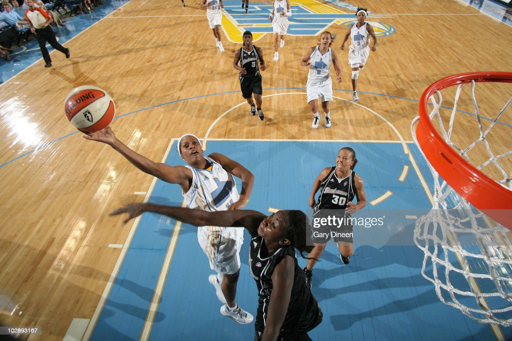Jia Perkins #11 of the Chicago Sky goes to the basket over Sophia Young #33 and Helen Darling #30 of the San Antonio Silver Stars during the WNBA game on July 14, 2010 at the All-State Arena in Rosemont, Illinois.