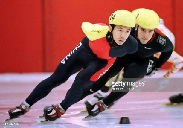 Jiajun Li from China rounds the corner as Daniel Weinstein from USA pursues him in the men's 1000 meter finals race at the 2000 Short Track Speed...