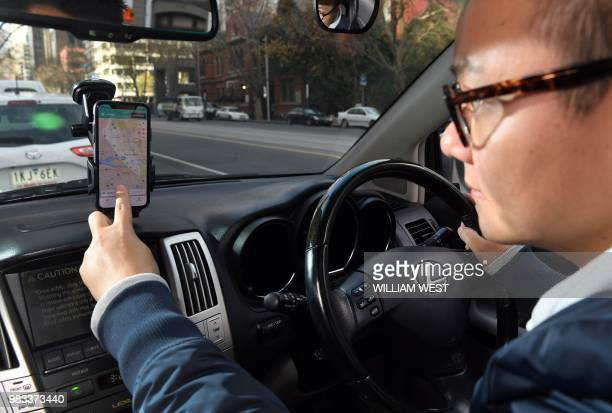 Jian Lu from Chinese ridesharing giant Didi Mobility demonstrates the Didi app on his smartphone in Melbourne on June 25 2018 Chinese ridesharing...