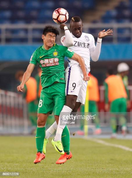 Jiang Tao of Beijing Guoan competes for an aerial ball with Mbaye Diagne of Tianjin Elion FC during the Chinese Super League match between Tianjin...