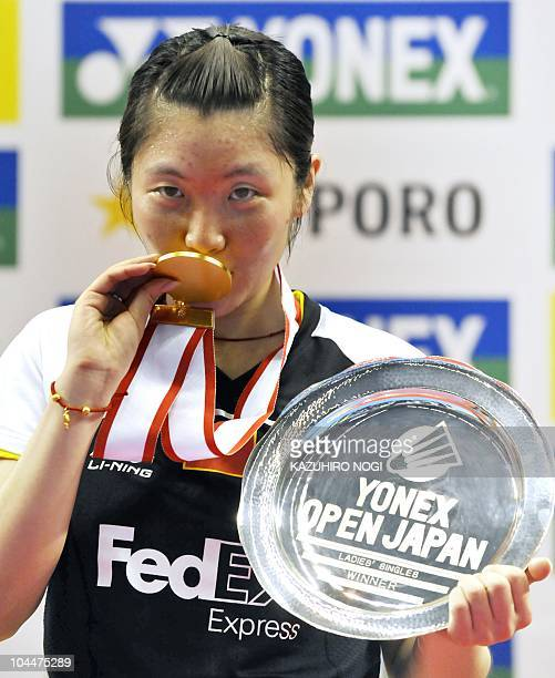 Jiang Yanjiao of China kisses with her winner's medal during the award ceremony for the women's singles final match against her Chinese fellow Wang...