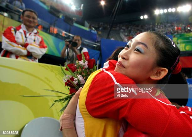 Jiang Yuyuan of China is is congratulated by a coach after competing in the women's artistic gymnastics team final at the National Indoor Stadium...