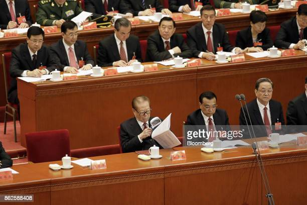 Jiang Zemin China's former president front row left holds a magnifying glass while reading as he sits alongside Li Keqiang China's premier and Yu...