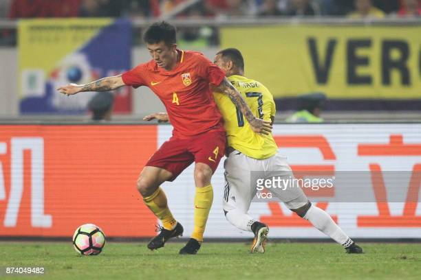 Jiang Zhipeng of China National Team and Edgar Pardo of Columbia National Team compete for the ball during the international friendly match between...