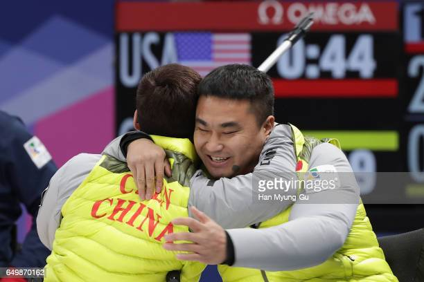 Jianxin Chen from China embraces teammate Haitao Wang from China after winning round robin session 11 in the World Wheelchair Curling Championship...
