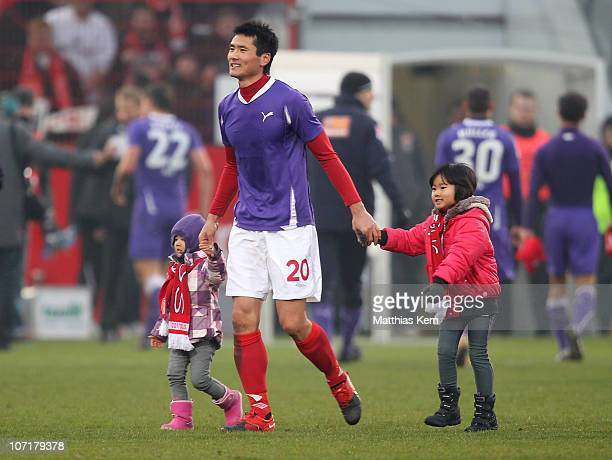 Jiayi Shao of Cottbus and his children walk over the pitch after the Second Bundesliga match between FC Energie Cottbus and Erzgebirge Aue at Stadion...