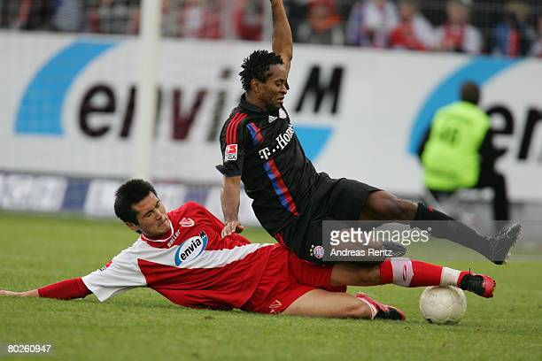 Jiayi Shao of Cottbus vies for the ball with Ze Roberto of Bayern Munich during the Bundesliga match between FC Energie Cottbus and Bayern Munich at...