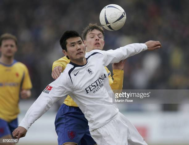 Jiayi Shao of Muenchen and Benjamin Siegert of Braunschweig vie for the ball during the match of the Second Bundesliga between Eintracht Braunschweig...
